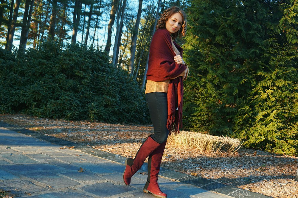 A blogger posing near the park, wearing a brown sweater, jeans, maroon boots and scarf.