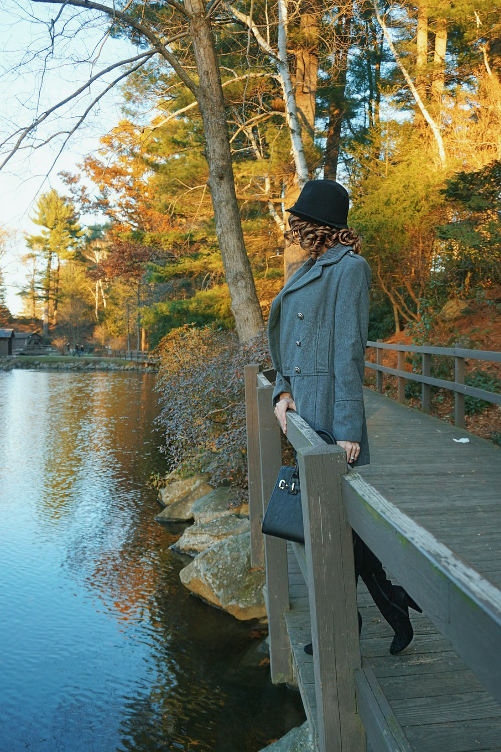 A fashion blogger looking at the pond, wearing black jeans, gray coat, black hat, and thigh high boots.