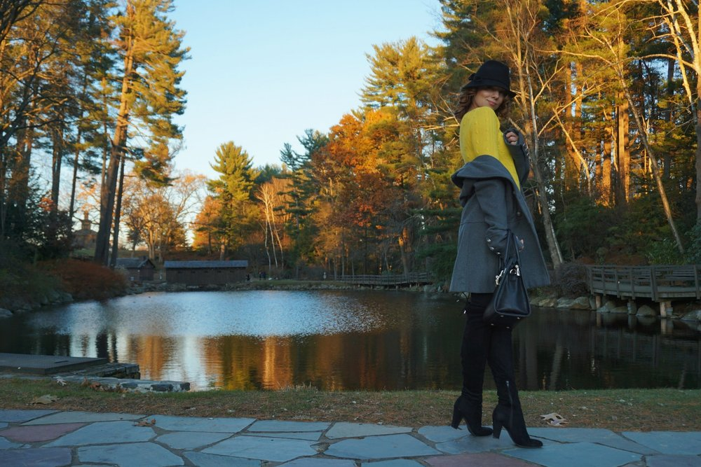 A fashion blogger standing in front of the pond, wearing an autumn cozy look.