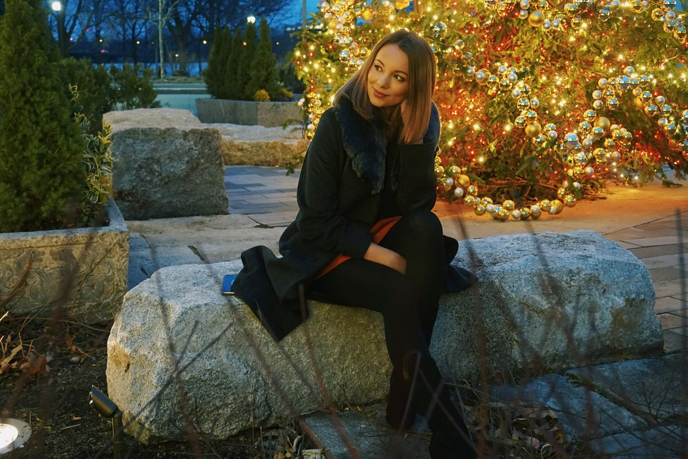 Fashion blogger sitting on a rock outside with the Christmas tree behind her.