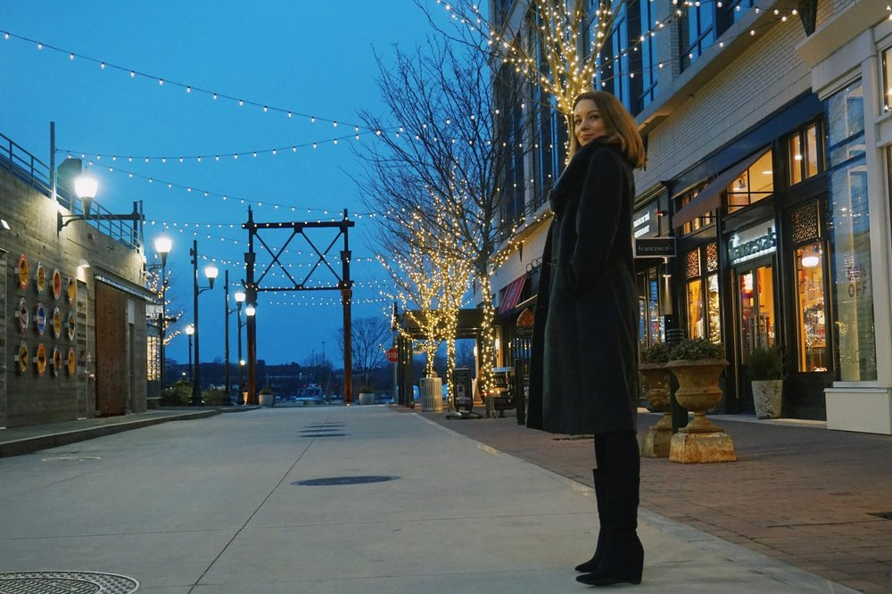 Blogger standing near beautiful restaurants covered with Christmas lights.
