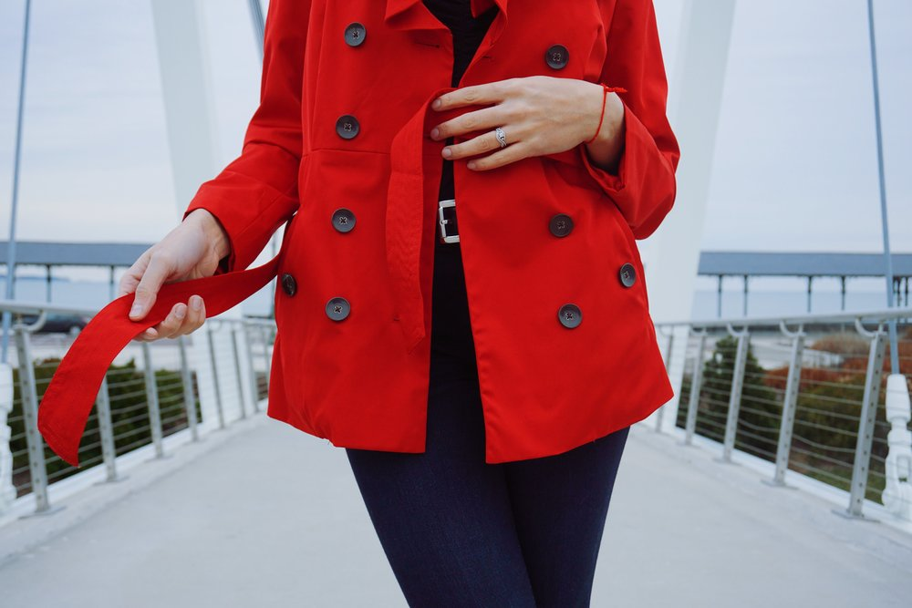 A close-up of a red coat with black buttons and red belt.