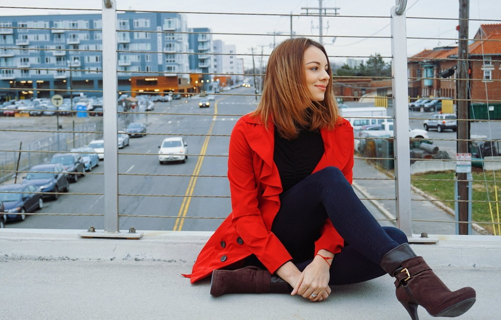 Girl sitting on the bridge, wearing a red coat, express jeans, black turtleneck, and brown high heel booties.