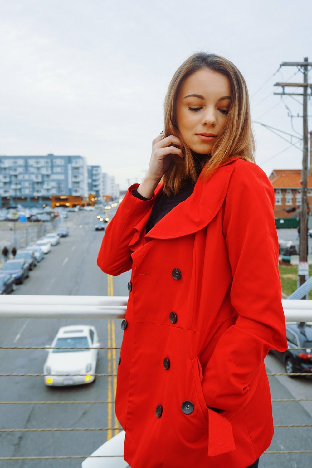 Beauty blogger looking down in the picture, wearing a red coat with ruffles in the front of it.