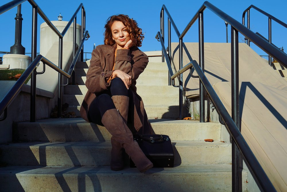 A fashion blogger sitting on the stairs, wearing a brown coat, dark denim, and brown boots.