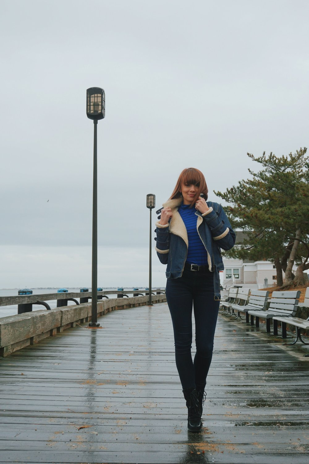 A fashion blogger wearing an all denim outfit, and walking down the boardwalk near the ocean.
