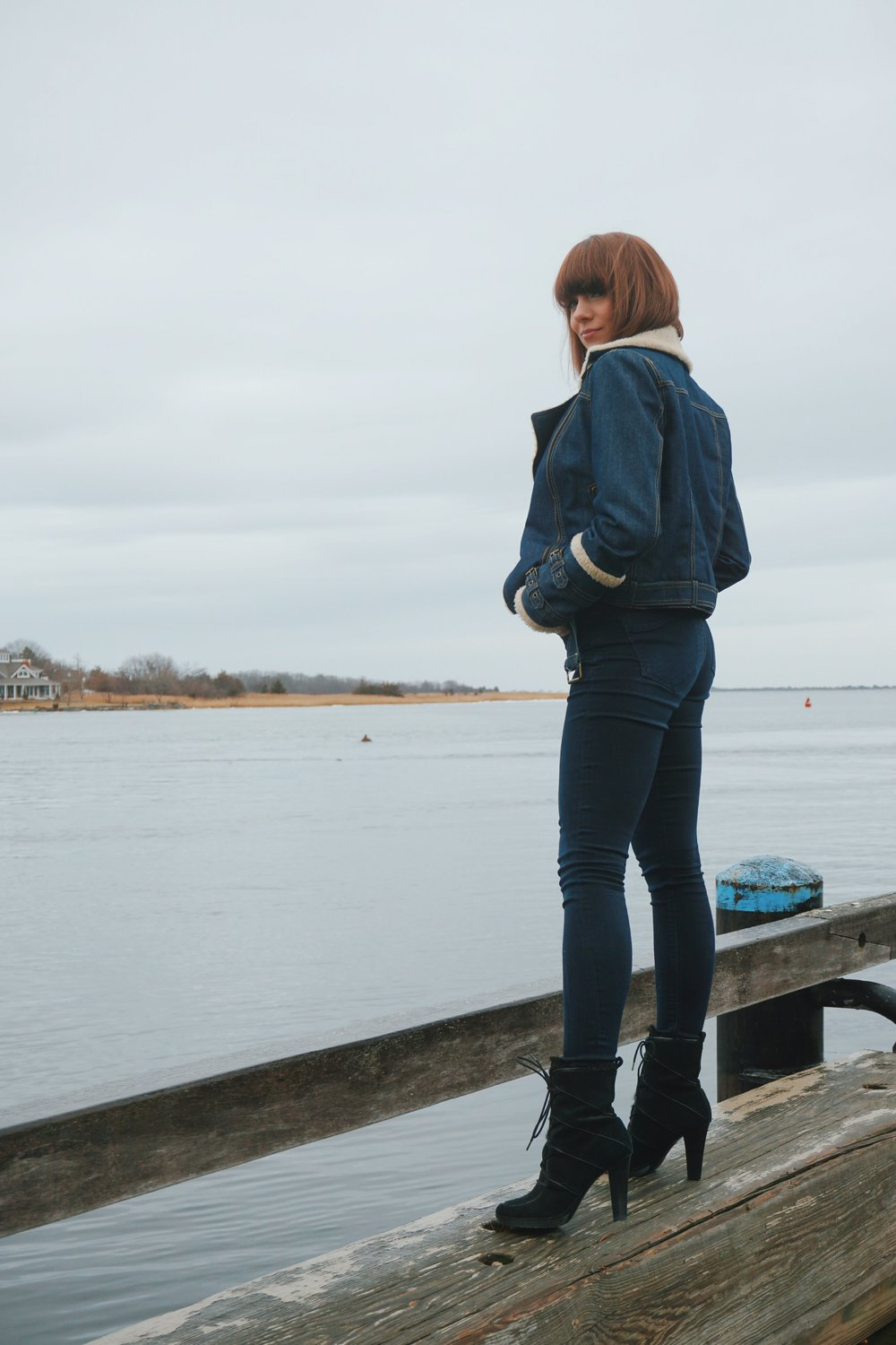 A blogger looking back at the camera, wearing expess jeans, winter denim jacket, and black high heel boots.