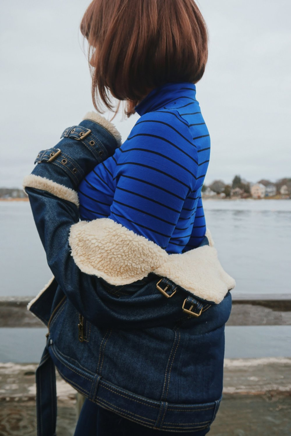 Details of an outfit: blue turtleneck with black stripes, winter denim jacket, jeans.