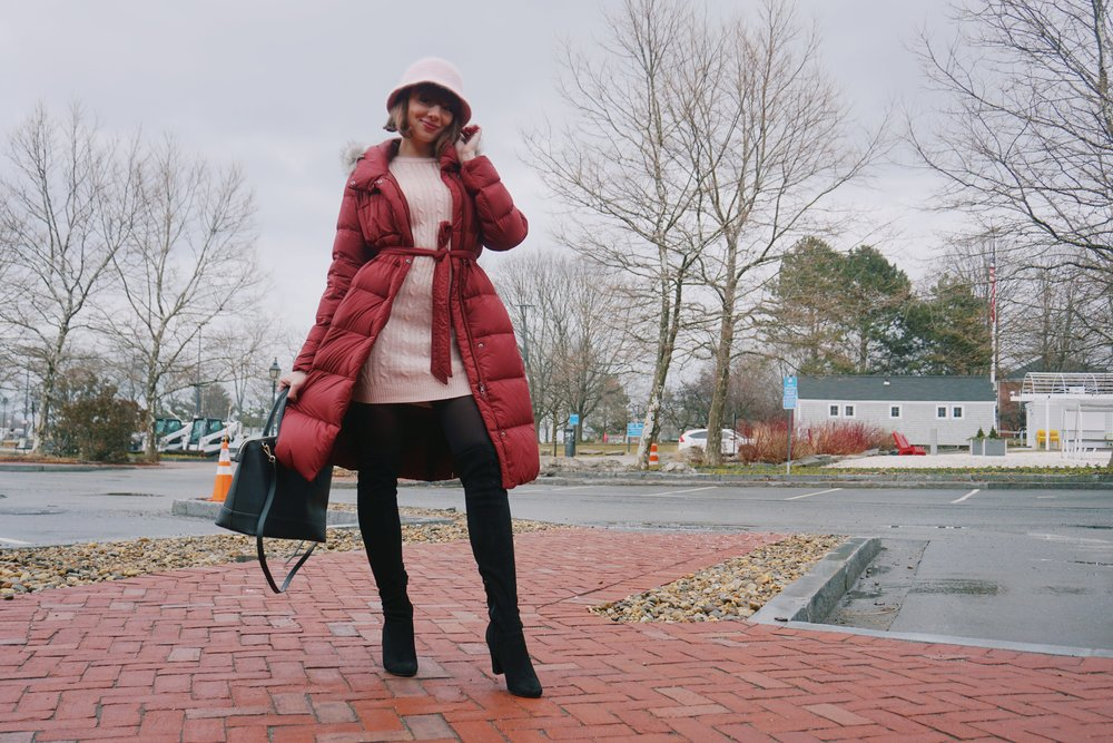 A blogger wearing a UniQlo winter coat, pink sweater dress, black over-the-knee boots, and a black bag.