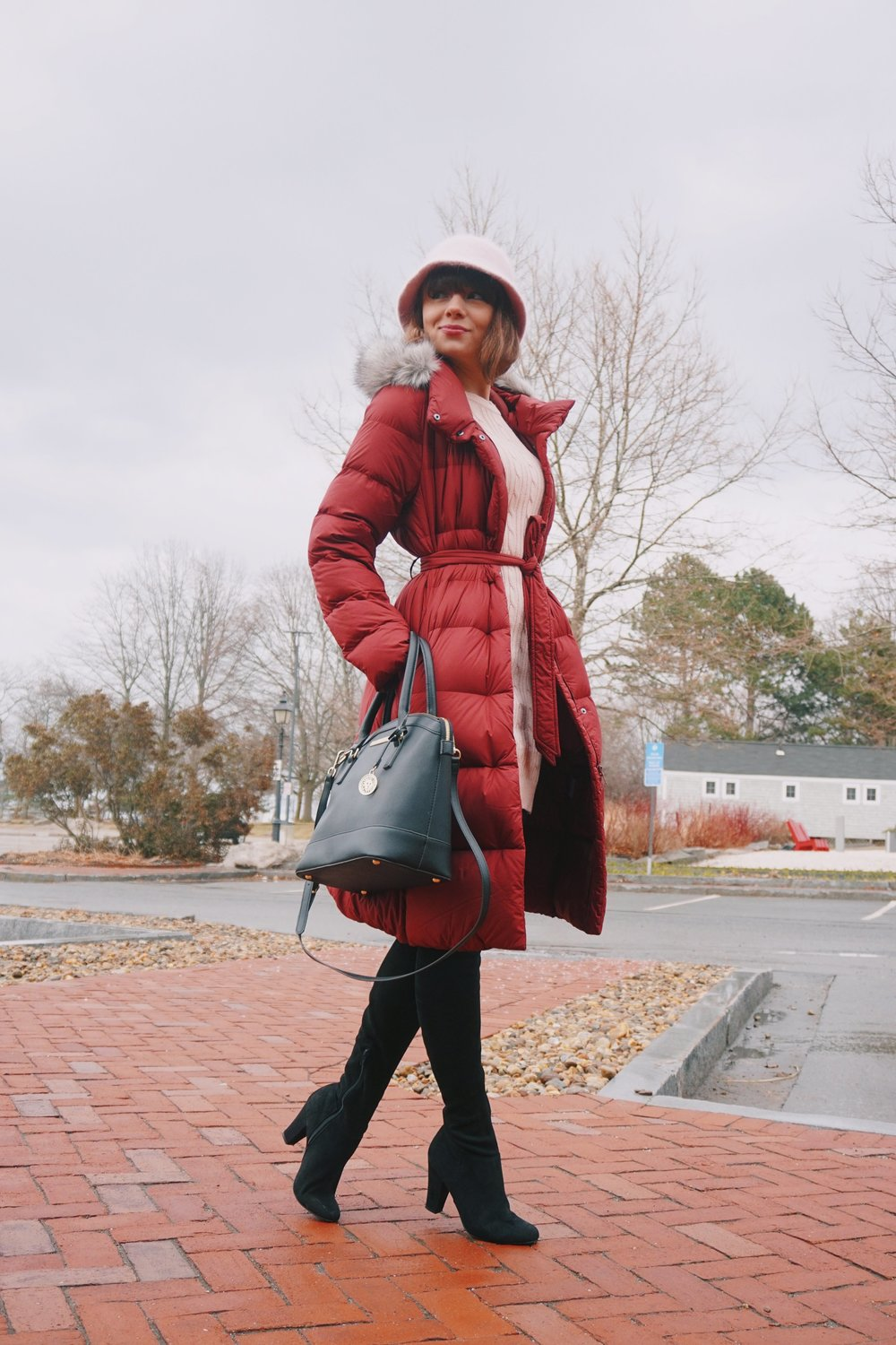 Winter outfit inspiration: craberry winter coat, black boots, black bag, and pink hat.