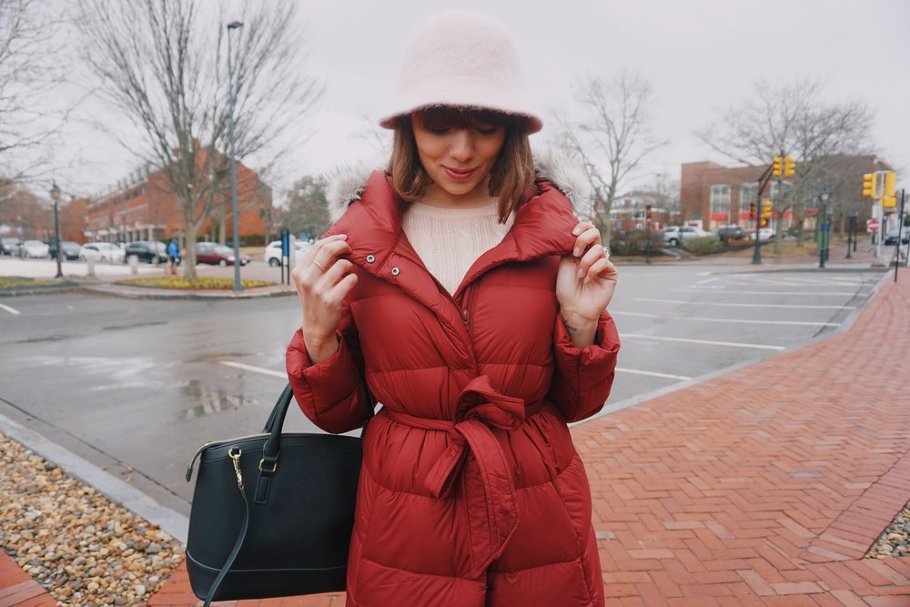 Blogger weaing a winter outfit: puffy winter coat, and pink hat.