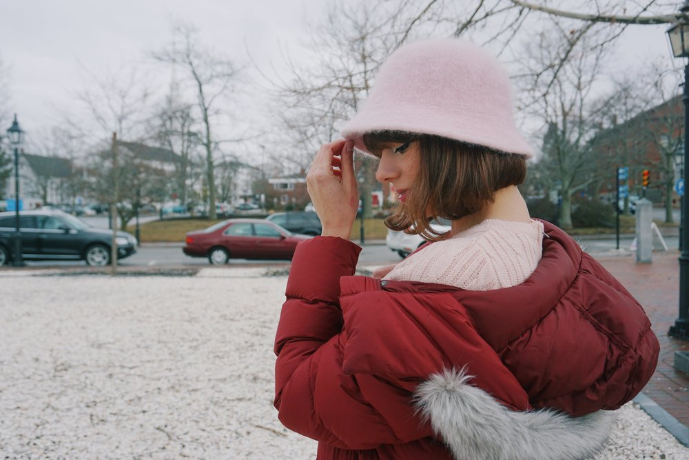 A photo of a blogger looking down, wearing a dark red winter coat and a pink hat.
