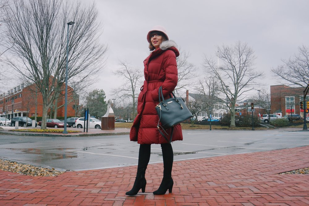 Fashion blogger posing on the street of Newburyport, wearing pink sweater dress, cranberry winter coat, over the knee high heel boots, pink hat, and a big black purse.