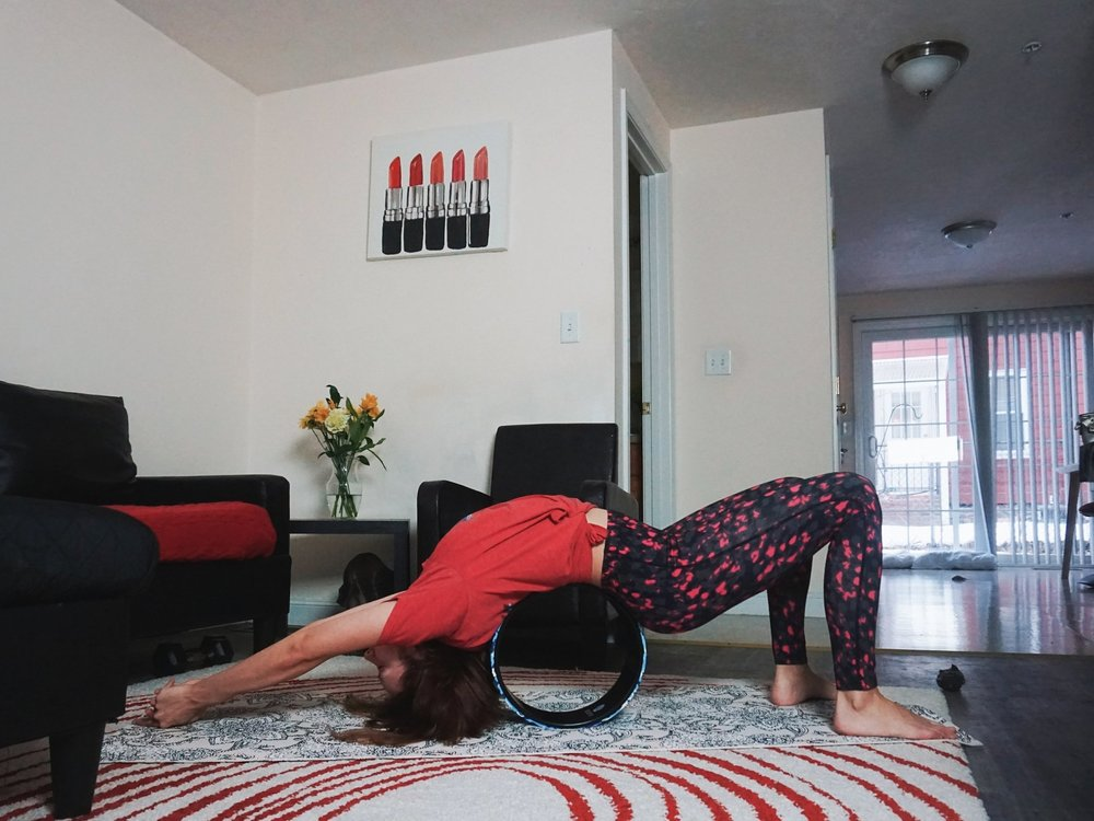 A blogger is stretching her back with a yoga wheel.