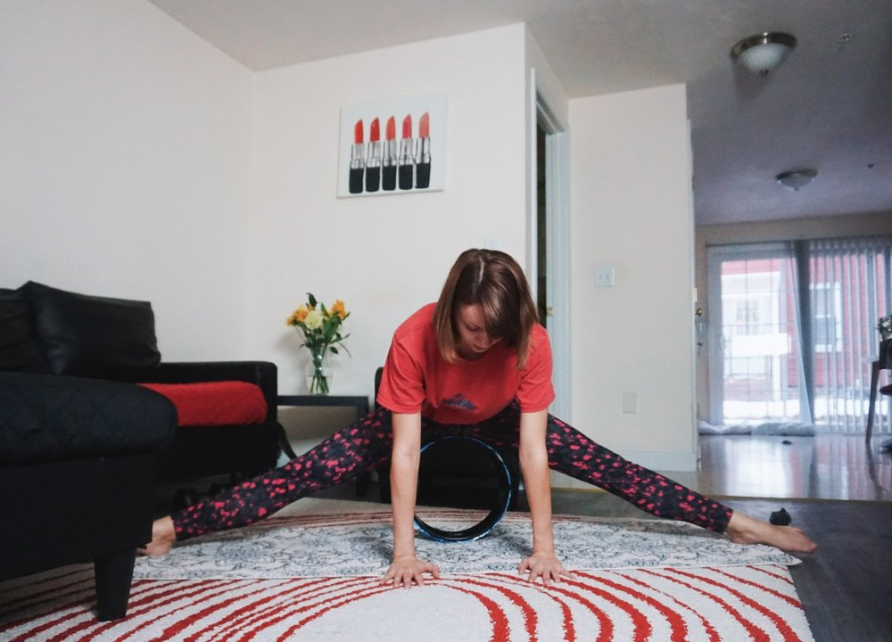 A beginner yogi is working on her middle split with the help of a yoga wheel.