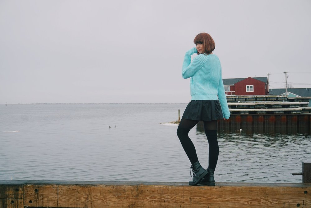 A girl posing near the ocean, wearing a blue sweater, black skirt, black tights and thight high socks, and black combat boots.