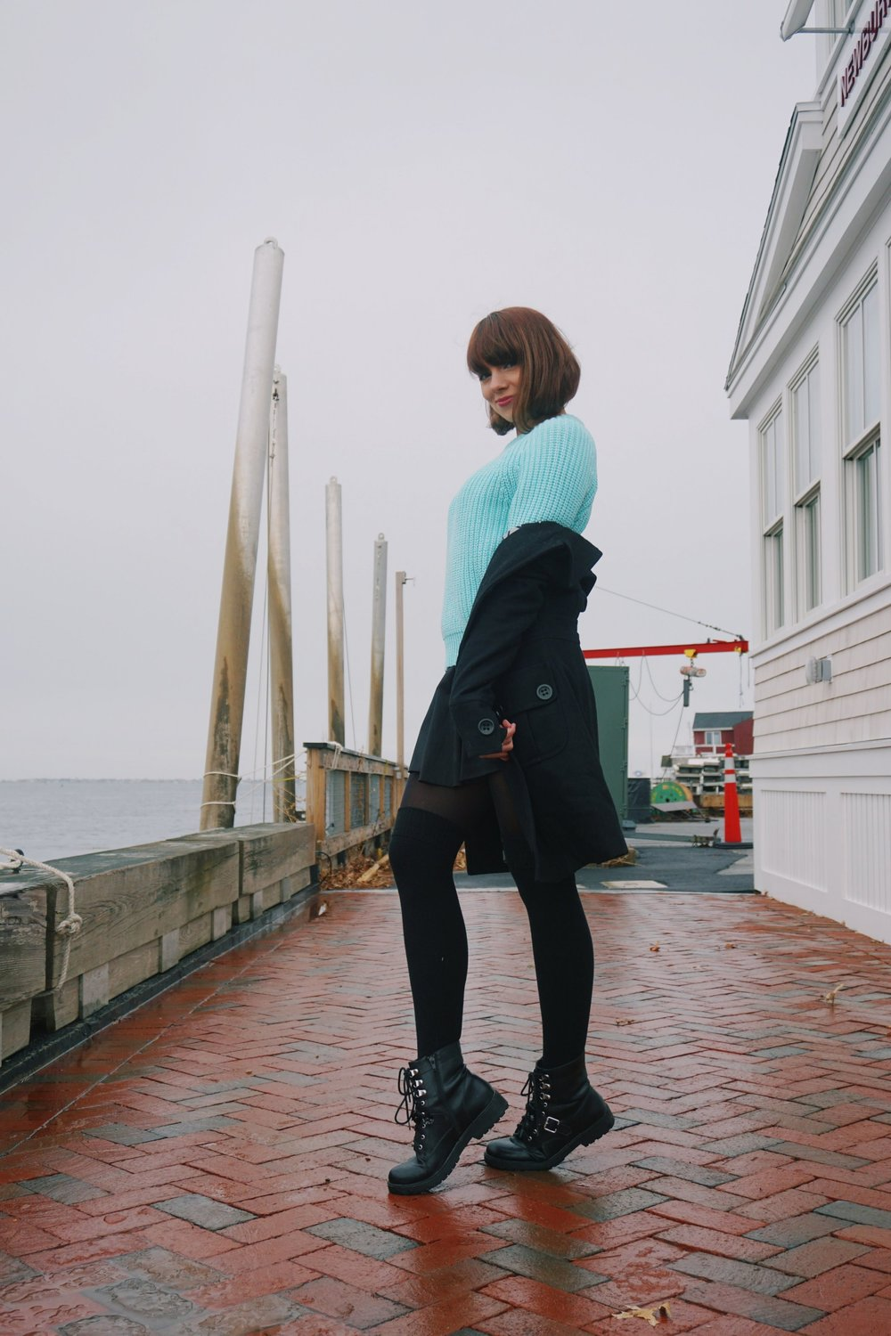 Winter outfit inspiration on a blogger: black coat, blue oversized sweater, short black skirt, black tights and over the knee socks, and black army boots.