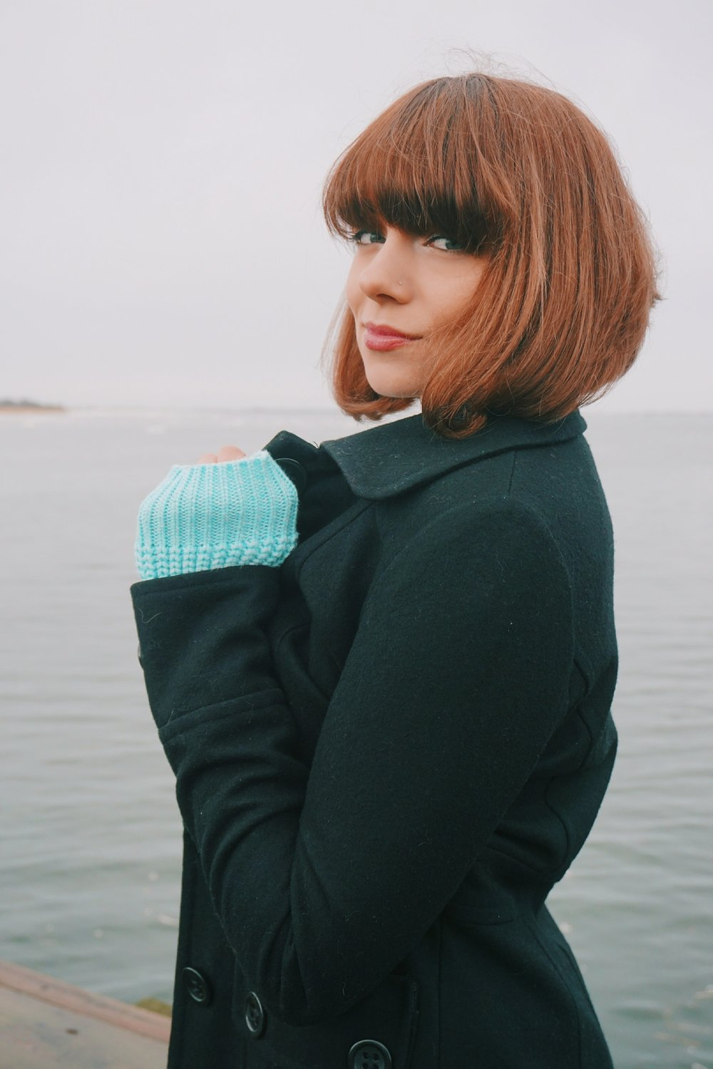 A portrait of a fashion blogger with short bob and bangs, who is wearing a blue sweater and a black coat in the photo.