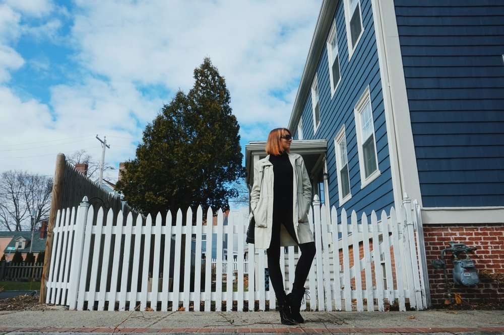 Fashion blogger posing by a white fence, wearing black turtleneck, black tight pants tucked into black faux-fur boots, black bag, and a nude trench coat.