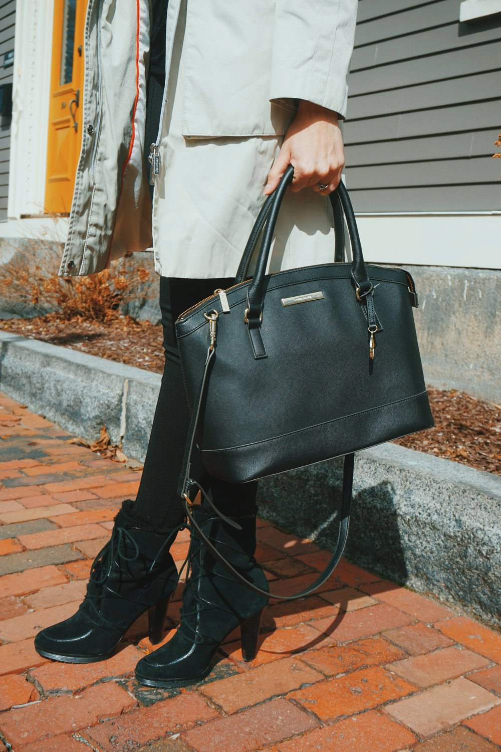 Details of an outfit : nude trench coat, black leggings, blck faux fur booties, and a big black bag.