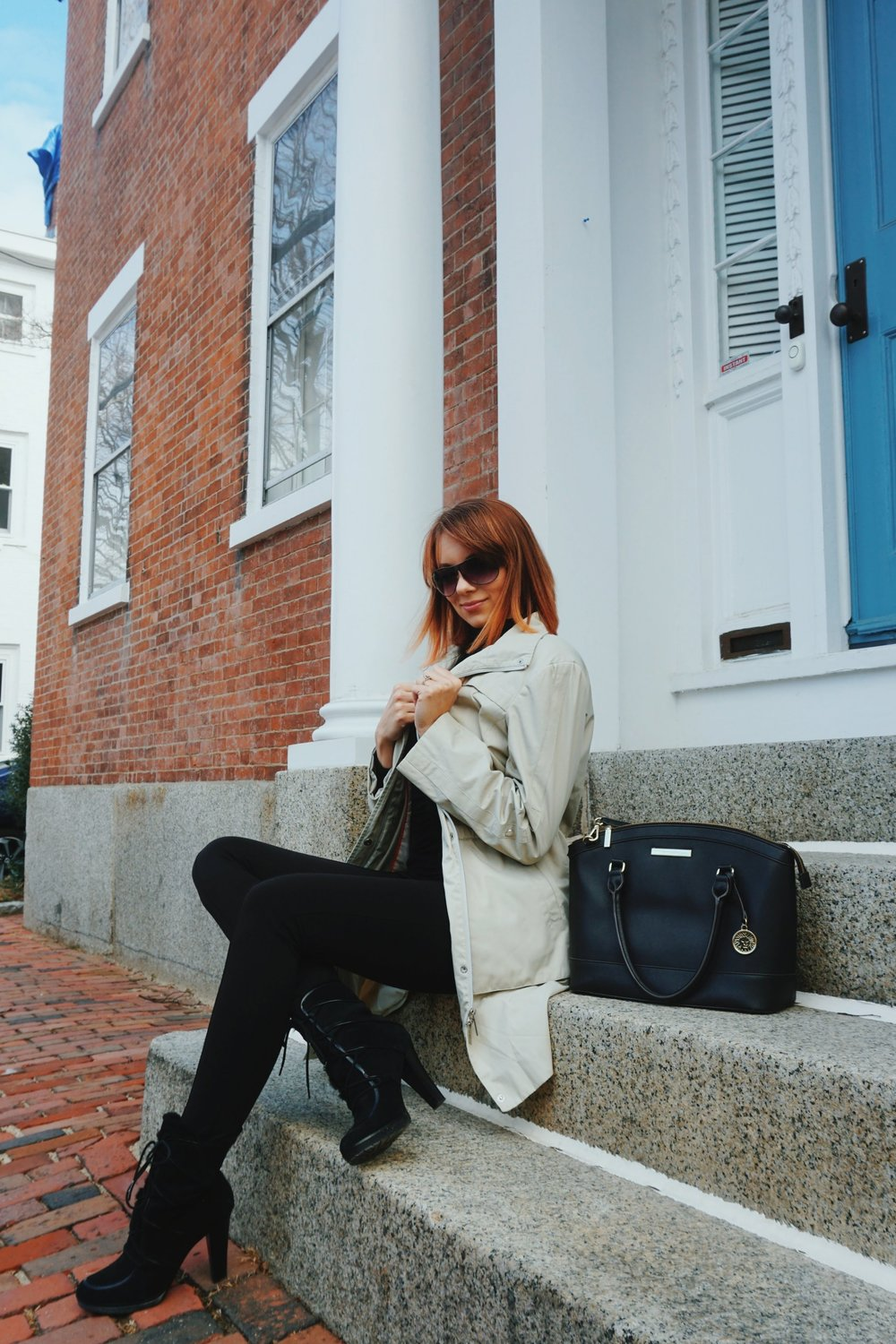 A blogger sitting on the steps in front of a Boston house, wearing an all-black outfit and a nude trench coat.