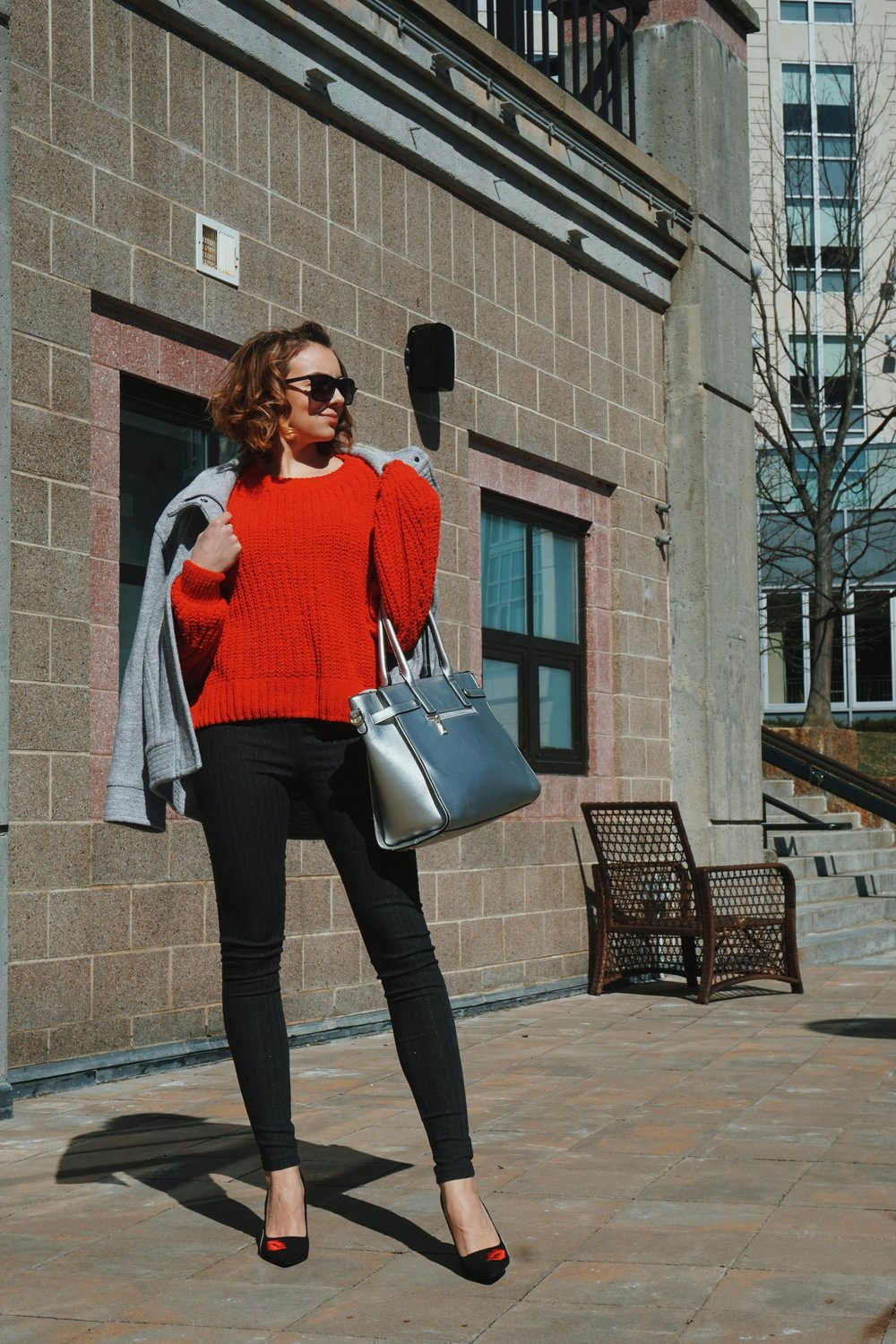 Blogger posing by a wall, wearing a red H&M sweater, light gray coat, dark gray pants, black heels, and a silver bag.