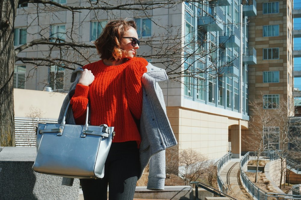 A girl looking to the side, wearing a Spring outfit: chunky red sweater, gray pants, gray coat, and silver bag.