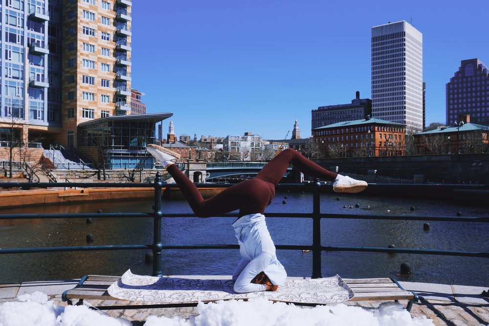 A girl is doing a headstand on a bench near the water canal in Providence.