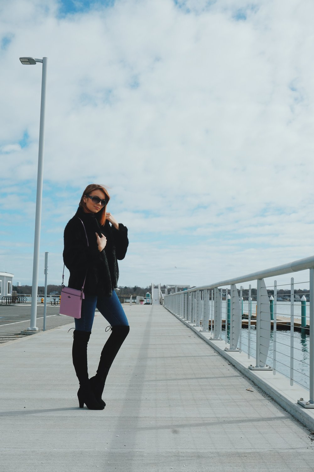 Blogger posing by the beach, wearing a black faux-fur coat, denim, over-the-knee black boots, and a blush/pink crossbody bag.