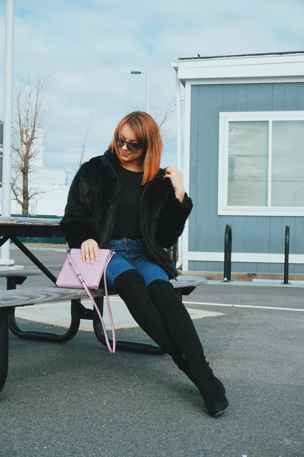 Girl sitting on a bench, wearing black faux-fur coat, denim jeans, OTK boots, and a pink crossbody bag.