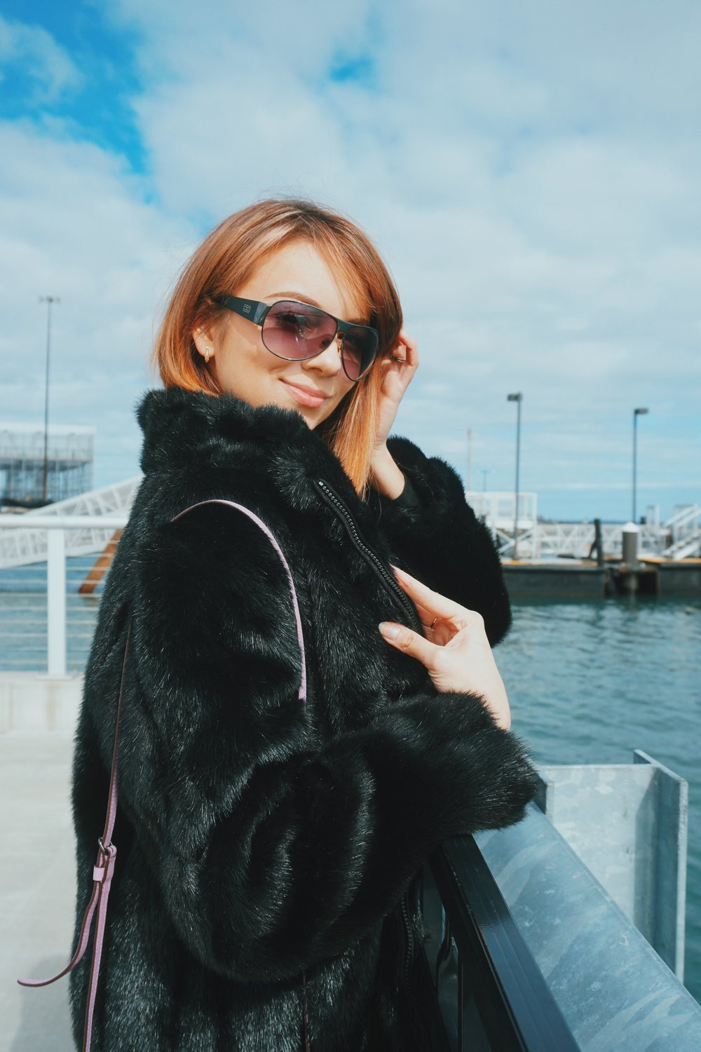 Fashion blogger looking in the camera, and wearing a black faxu fur coat.