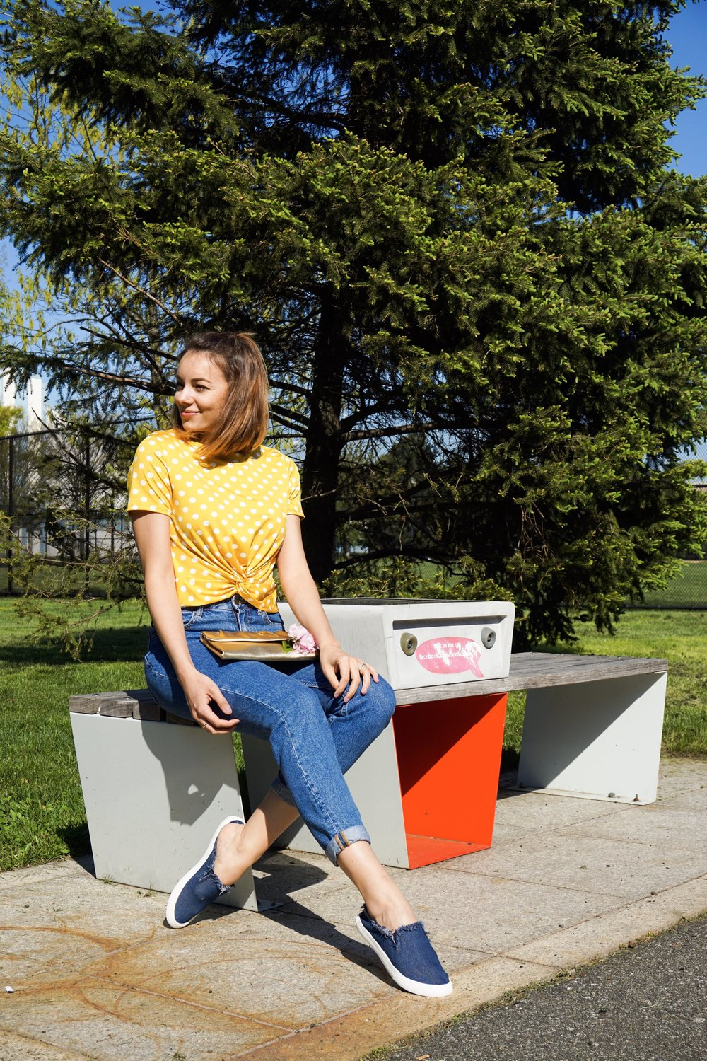 A girl sitting on the bench in the park, wearing a yellow crop top, blue jeans, and denim slips ons.