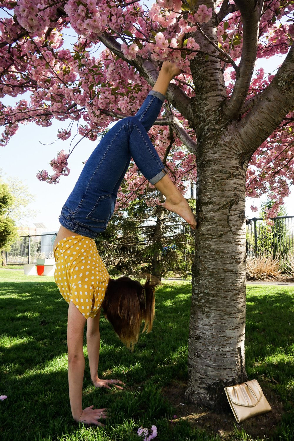 A girl doing a headstand near a tree.