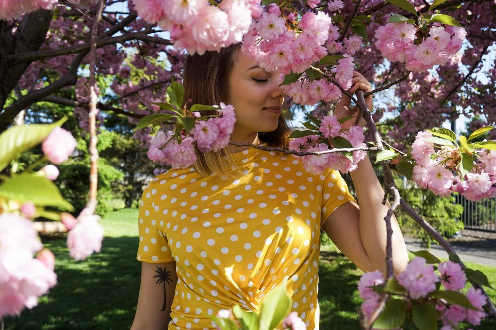 Girl is sniffing flowers on a tree, wearing a cute yellow top.