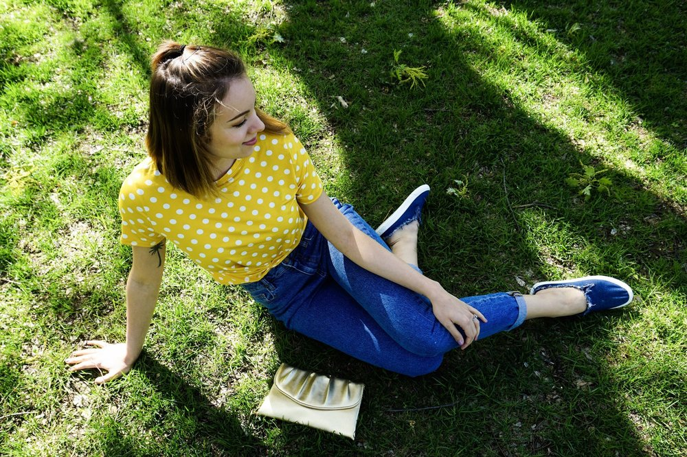 A photo from up top looking at a girl who is sitting on the grass. She is wearing a yellow crop top, jeans, denim slip ons, and a golden clutch that is laying on the grass.