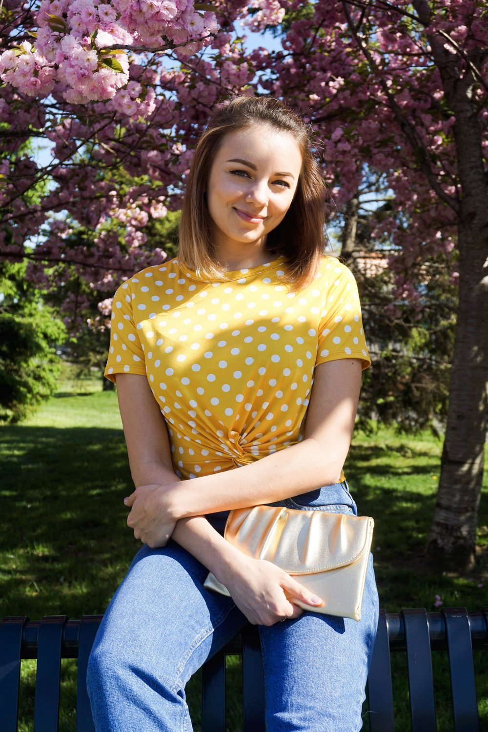 A blogger looking at the camera, wearing a yellow and white polka dot crop top, jeans, and a gold clutch.