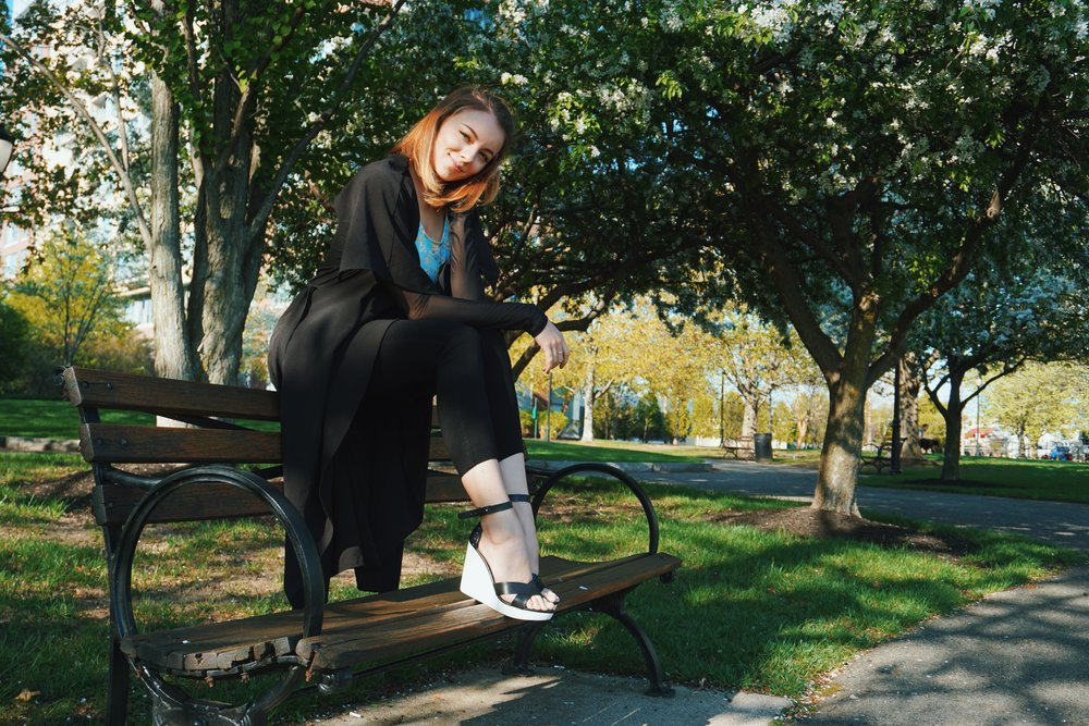 A girl sitting on a bench who is wearing black capris, black duster, blue top, and black and white wedges.