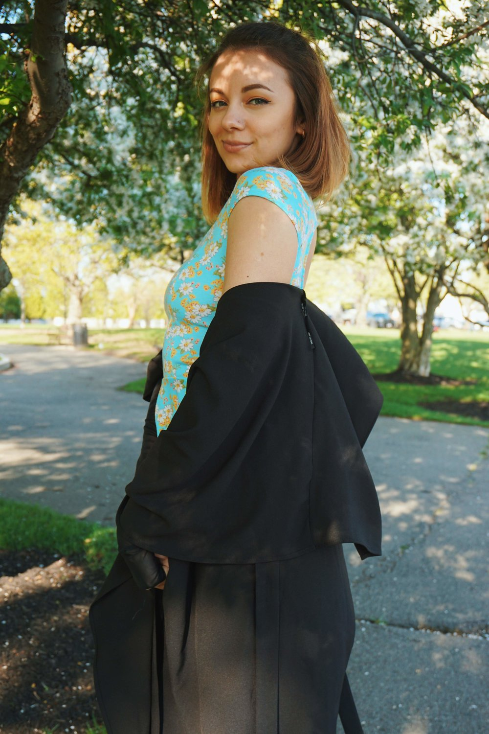 A side photo of a fashion blogger who is wearing a blue top, black capris, and black duster.