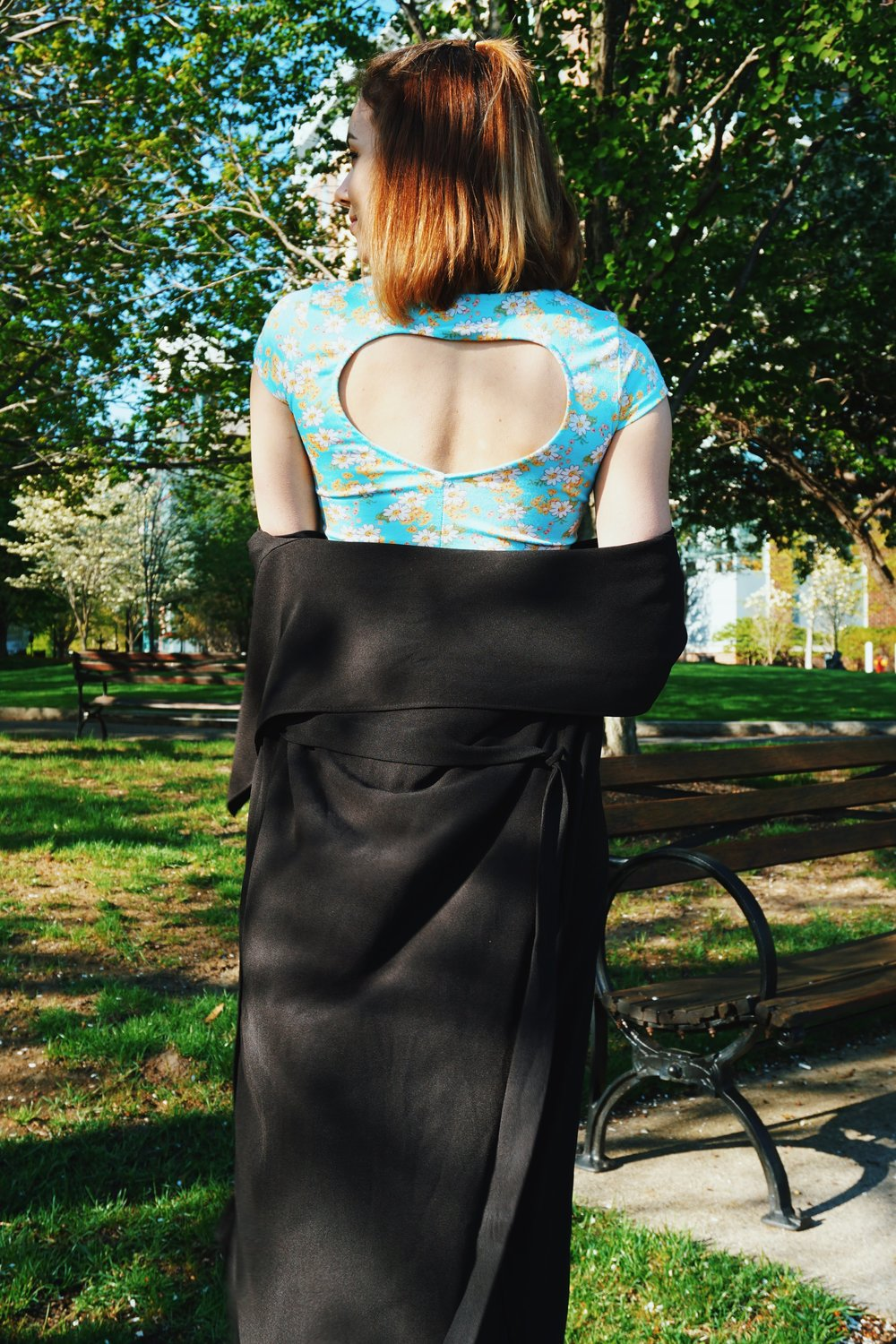 A photo of a fashion blogger's outfit: blue top with a heart-shaped cutout and a black duster.