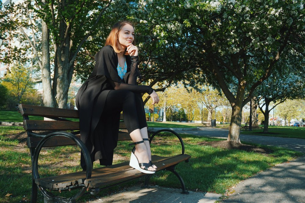 A girl sitting on a bench in a park, in a cute and elegant summer outfit.