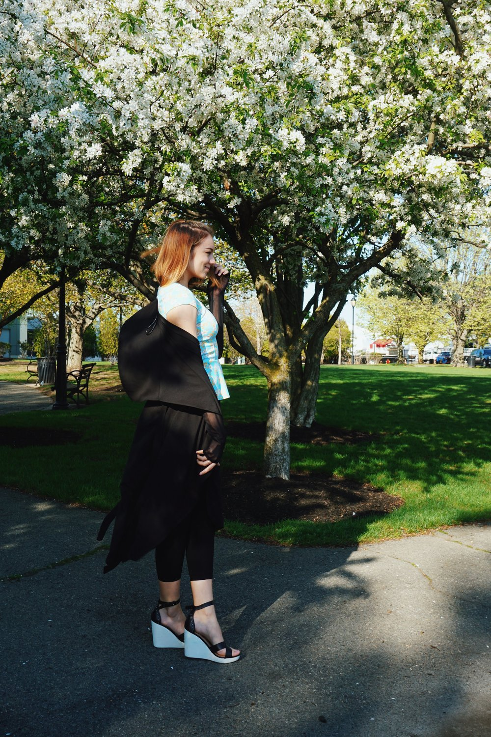 A side photo of a girl in the park, wearing a black duster, blue top, black capris, and black and white wedges.