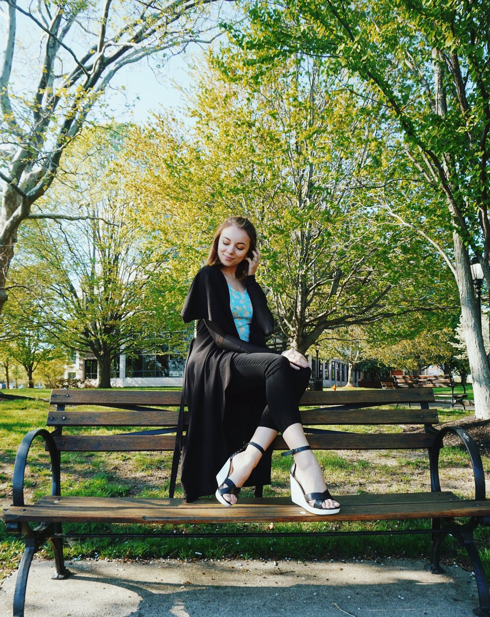 A girl sitting on a bench of the park in a stylish summer outfit.