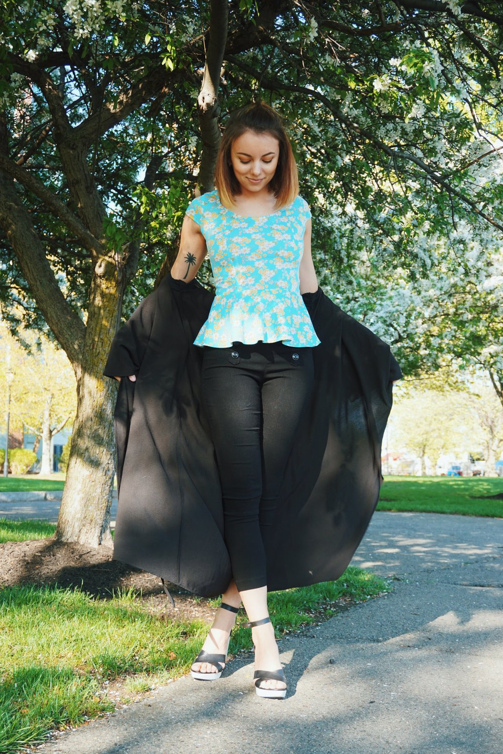 A photo of a girl in a cute blue top with ruffles, black capris, black duster.