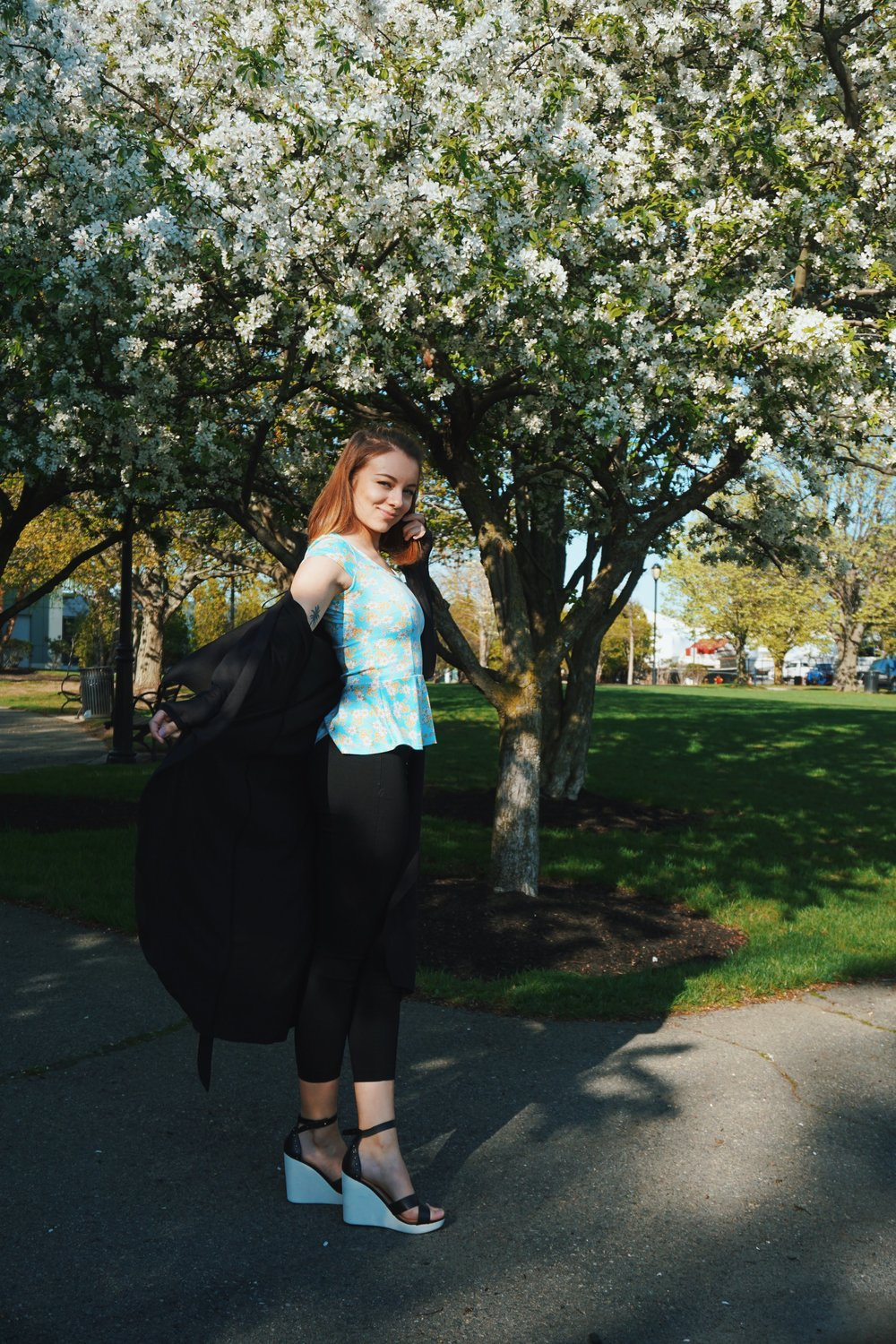 A blogger in a park posing for a shoot, wearing a blue top with white little flowers on it, black duster, black capris, and black and white wedges.
