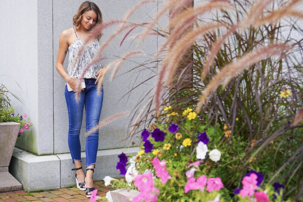 A blogger posing near a building and flowers.