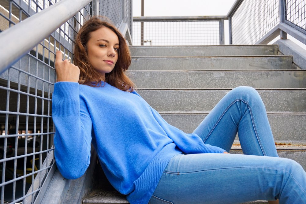Blogger sitting on the stairs, wearing a blue sweater and jeans.