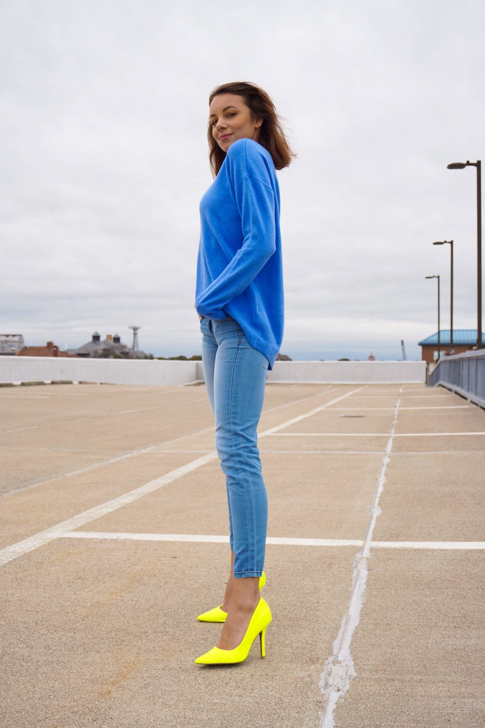 A girl posing on a top floor of a garage, wearinng a blue sweater, light denim pants, and neon heels.