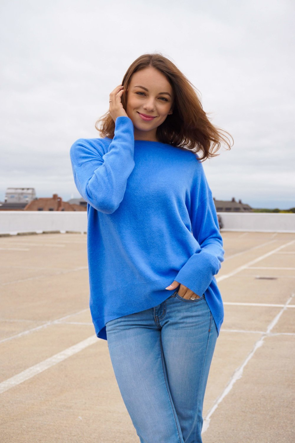A close up of a girl looking at the camera, wearing a blue sweater, blue jeans.
