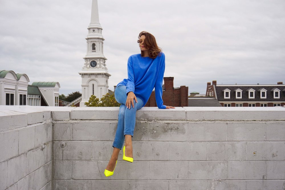 Blogger sitting on the edge of a wall, wearing a blue sweater, jeans, and neon high heels.