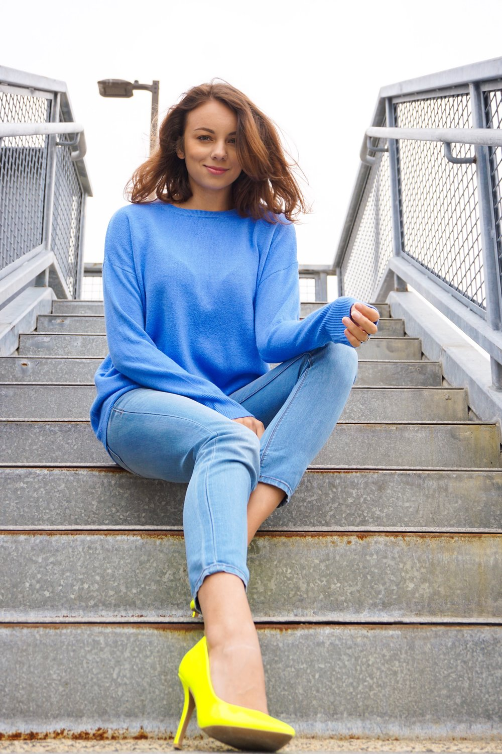 A girl sitting on the stairs, wearing an all blue autumn look.